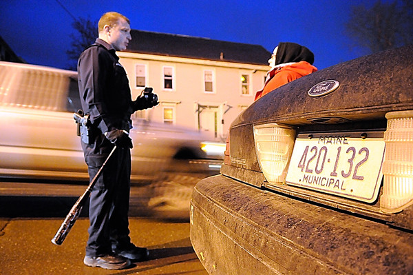 Carrying a baseball bat taken from an apartment, Bangor police Patrolman John Robinson talks to a passerby late Tuesday afternoon, Dec. 21, 2010, before she was allowed to  enter a multi-unit apartment complex at 165 Hammond St. in Bangor where her mother lives. A number of Bangor police converged on this address in response to an incident (Bangor Daily News/John Clarke Russ)