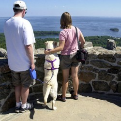"""I ... SAW THREE ISLANDS IN A BAY""    Edward and Jennifer Smith from Plattsburg, N.Y., enjoy the view of Camden from the tower on Mount Battie on Monday. Between them is their dog Molly. (BANGOR DAILY NEWS PHOTO BY LINDA COAN O'KRESIK)"