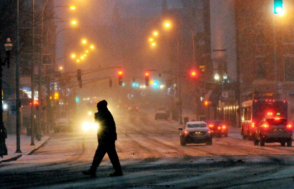 A man crosses Main Street in Worcester, Mass., near City Hall, as the snow falls early Sunday evening Dec. 26, 2010. (AP Photo/Worcester Telegram & Gazette, Rick Cinclair)