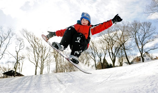 Lance Johnson, 11, takes to the air jumping his snowboard off a ramp built by his father, Eric, not pictured, at Washington Park in Groton, Conn., Monday, Dec. 27, 2010. Sunday's overnight blizzard dumped about 6-8 inches of snow in the region. (AP Photo/The Day, Sean D. Elliot) MANDATORY CREDIT; MAGS OUT; INTERNET OUT; NO SALES