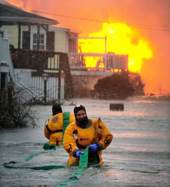 ** ADDS ID'S OF FIREFIGHTERS ** Scituate Firefighters John Reidy, front and Joe West lay a hose down a street filled with coastal floodwaters to fight a house fire during a snowstorm in Scituate, Mass., Monday, Dec. 27, 2010.  (AP Photo/The Patriot Ledger, Greg Derr)   BOSTON GLOBE OUT. BOSTON HERALD OUT. TV OUT.