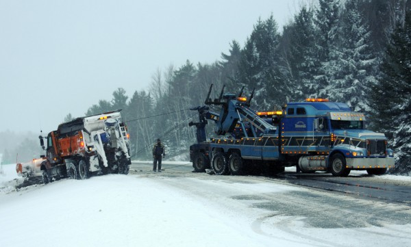 Two wreckers pull a Maine Department of Transportation plow truck loaded with salt back on to I-95 near the north bound Kelly Road ramp in Orono on Monday, December 27, 2010 during a a lull in blizzard conditons. (Bangor Daily News/Kevin Bennett)