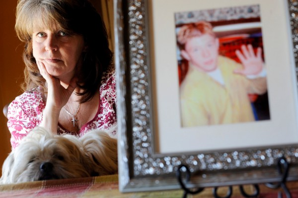 Cheryl Morin and her dog Tiny sit near a family photo of her son, Joe Day, then 16. Day took his life in November 2005 when he was 19 years old. Morin established the JD Foundation to heighten suicide awareness and prevention.  (BANGOR DAILY NEWS PHOTO BY JOHN CLARKE RUSS)