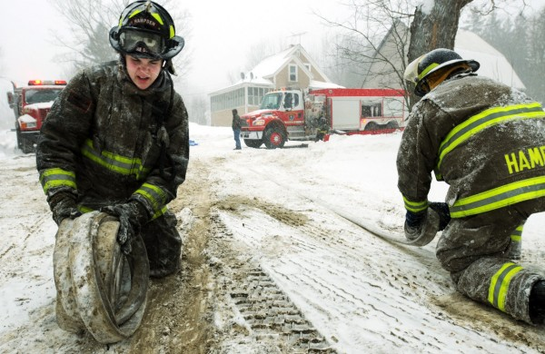 Hampden firefighters Jordan Stewart, left and Matt Thomas roll hoses in the snow covered street in front of 310 North Road in Winterport on Monday, December 27, 2010 after putting out a fire at that location. Numerous departments responded to the report of a smoked filled home. Two pets perished in the fire that was contained to the living room where a christmas tree is suspected starting the blaze. (Bangor Daily News/Kevin Bennett)