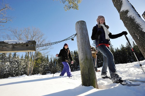Hannah Richards of Bangor and Sarah Carter of Old Town lead Jonathan Holland and infant son Austen (both partially obscured) and Carter's fiance Robby Lambert (cq) (not pictured) of Old Town for a trek over the fresh snow at the Rolland F. Perry City Forest Tuesday. (Bangor Daily News/John Clarke Russ)