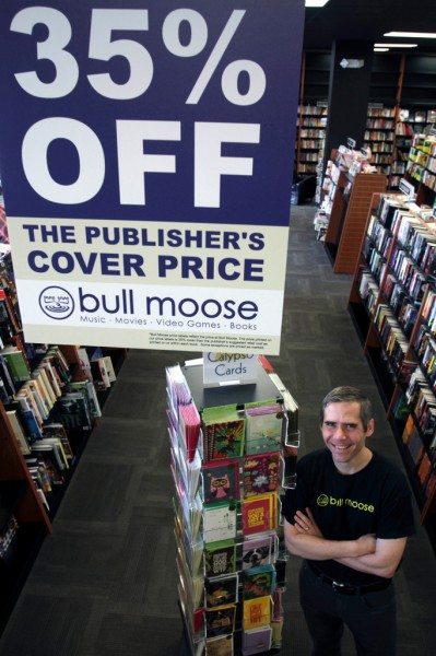 In this Tuesday, Dec. 7, 2010 photo, store owner Brett Wickard poses at Bull Moose in S. Portland, Maine. As the owner of the Bull Moose chain of music stores, he is going against the grain in expanding into book sales at a time when others seem to be getting out of it. (AP Photo/Pat Wellenbach)