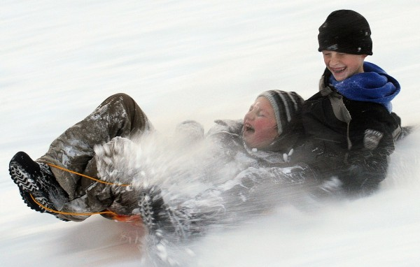 Caden Buzzard, 8, (left) and his cousin Izak Collins, 10, slide down Watchmaker Hill while out sledding Thursay afternoon.  The boys moms are two of the four Black and Hall sisters who were enjoying the winter fun with their fourteen children. (Bangor Daily News/Gabor Degre)