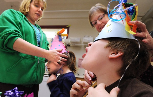Michael Gallant, 8, (right) gets some help with his new hat from his grandmother Holly Bricker while his mother Jennifer Gallant (left) helps Michael's sister five-year-old Emma.  They came to the New Years Eve celebration at the Maine Discovery Museum Friday. &quotWe did this last year too and we had a blast.&quot Jennifer Gallant said.  Children made hats, noise makers drums in preparation for their early ringing in of the New Year. (Bangor Daily News/Gabor Degre)