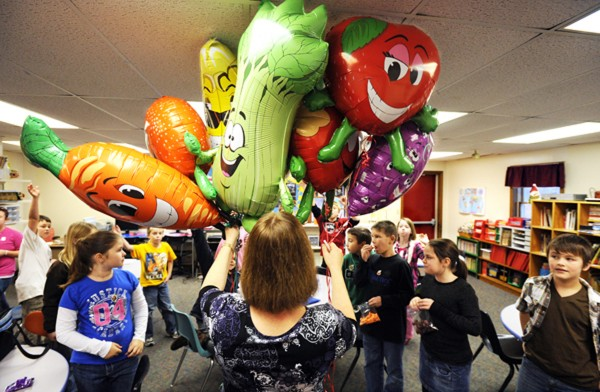 Morison Elementary School nurse Sue Parker (center) solicits votes on which helium-filled balloon character Deb Dearborn's fourth-grade class wants for its class mascot earlier this month. The balloons serve as reminders of the school's 5-2-1-0 Let's Go! program, which is designed to promote healthy living. Parker was awarded a federal grant to purchase snowshoes to allow students the opportunity to explore the school's walking trails once they are covered with snow.