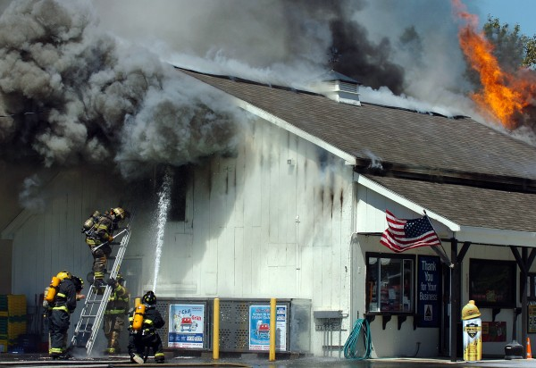 Firefighters work at the scene of a fire at the Big Apple store in Corinna on Thursday, Aug. 19, 2010. &quotA customer came running in saying there was smoke coming out of the building,&quot said store manager Gilbert Andrews. Andrews and the other employee who was working got out safely as did the store's customers.