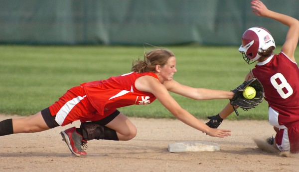 South Portland short stop Danica Gleason (left) reaches in an attempt to tag Bangor's Eliza Estabrook in the seventh inning of their Class A softball championship game at Saint Joseph's College in Standish on Saturday, June 19, 2010. Estabrook was safe on the play and South Portland won 1-0.