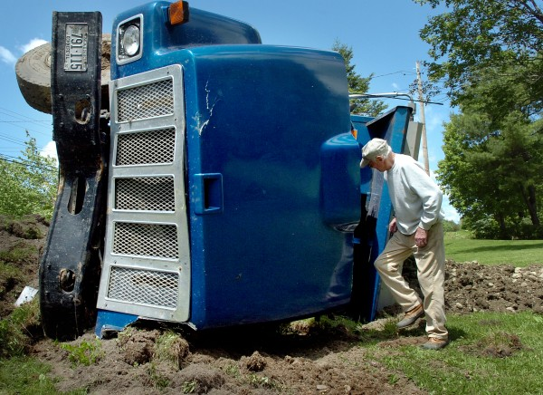 &quotI was glad I wasn't mowing my lawn,&quot said Robert Sherwood of Eddington as he examined a commercial truck transporting gravel which overturned in his yard Monday, June 7, 2010. Truck driver Haley Collins said that he was traveling from Milford to Eddington on Route 9 when a passenger car crossed the center line, causing a collision. Penobscot County Sheriff's Office Deputy Sheriff Daren Mason said that the driver and passenger of the car sustained injuries but that they were not life-threatening.