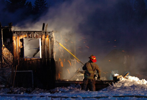 Lt. Josh Lilley of the Hudson Fire Department picks apart the remains of a Glenburn home on the Hudson Road that was destroyed in a fire Thursday evening, Jan. 7, 2010. According to Capt. Gene Hamm of the Glenburn Fire Department, the house was fully involved upon arrival and no one was injured in the blaze.