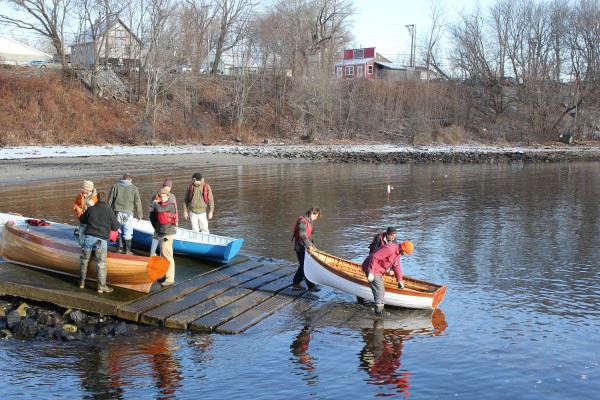People from the Apprenticeshop, a nonprofit wooden boatbuilding school in Rockland, carried six handmade boats down a snowy ramp Friday morning before apprentices, interns and members of the public paddled the newly-finished boats around the harbor.