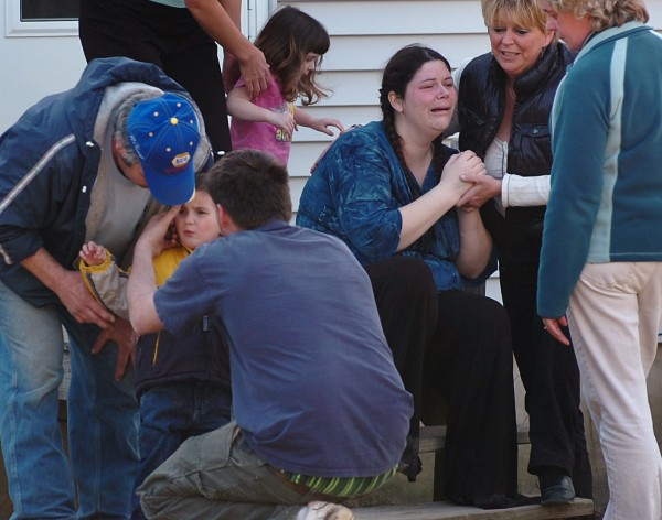 Logan Knight, 3, (lower left) is surrounded by family members after he was found in the woods near his home as his mother Nicole Dammier (third from right) is comforted by family and friends at their Mud Creek Road home in Lemoine on Wednesday, March 17, 2010. The boy was found by a neighbor safe but scared in the woods about 800 yards from his home after he wandered off with his dog.