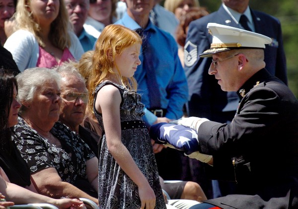 Maj. Michael Henderson presents Vianca Popkowski, 8, the daughter of Lt. James Popkowski, 37, with a flag at the former Marine's interment Tuesday, July 13, 2010 at Grindstone Road Cemetery in Medway. Popkowski died last week in a shooting involving law enforcement officials in Augusta that is currently under investigation.