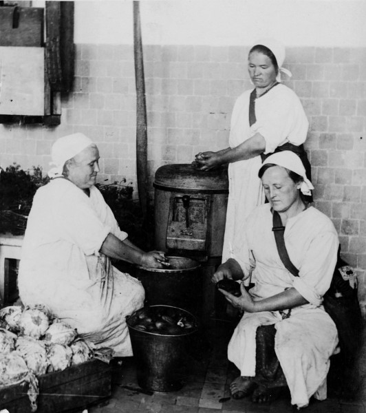 Women peeling potatoes and working in the kitchen of sanitarium for children with tuberculosis in Odessa.  Straps across their shoulders hold masks to put on in case of a gas attack.