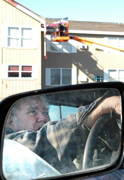 &quotI don't see anything wrong with this place,&quot said Ernie Julien, 81, (reflected in mirror) as he watches the roof being dismantled at the New Stable Inn in Brewer on Wednesday, Jan. 27, 2010 where he has been living for the past six years. &quotIt's the city that's doing all the damage,&quot Julien continued who, like many others living at the inn long-term, has no where to go in the wake of storm damage to the building. The City of Brewer contemned the motel Wednesday and the inn's managers asked tenants to return their keys and move out.