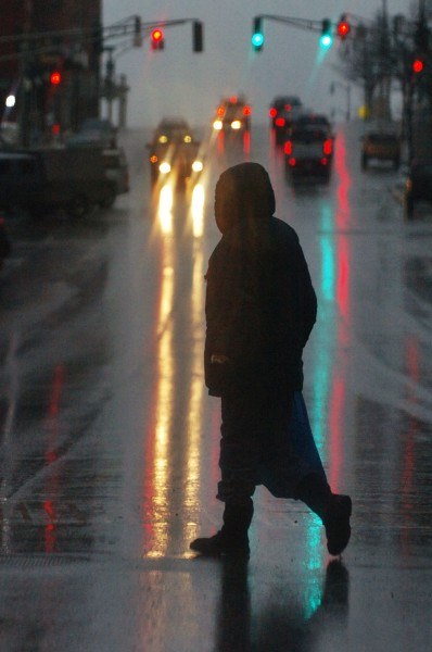 A pedestrian makes her way across Main Street in downtown Bangor on Monday, Jan. 25, 2010 as a steady rain and high wind gusts moved into the area. Rainfall is expected to taper today as skies remain overcast and a high near 36 degrees according to the National Weather Service.