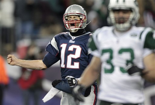New England Patriots quarterback Tom Brady, left, celebrates a touchdown by teammate Aaron Hernandez against the New York Jets during the second half of an NFL football game, Monday, Dec. 6, 2010, in Foxborough, Mass. At right is Jets safety Eric Smith. (AP Photo/Charles Krupa)