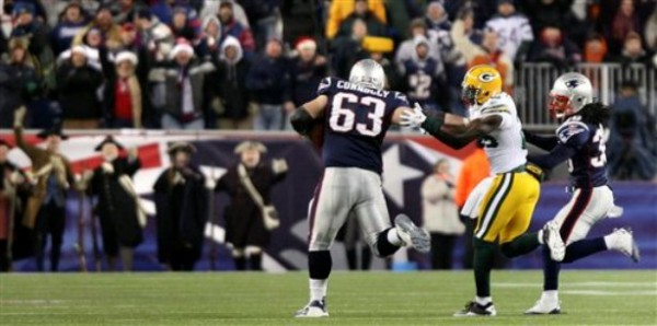 New England Patriots offensive lineman Dan Connolly (63) straight arms Green Bay Packers safety Charlie Peprah, center, on his way to the end zone on his touchdown during the second half of an NFL football game in Foxborough, Mass., Sunday Dec. 19, 2010.  The Patriots won 31-27.  At right is Patriots safety Sergio Brown.(AP Photo/Tim Cook)