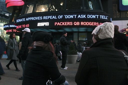 Cassandra Melnikow, foreground left, and her sister Victoria Melnikow,  right, sit in New York's Times Square as news of the Senate approving the repeal of &quotDon't Ask Don't Tell&quot is displayed outside ABC Television's Times Square studios Saturday Dec. 18, 2010. (AP Photo/Tina Fineberg)