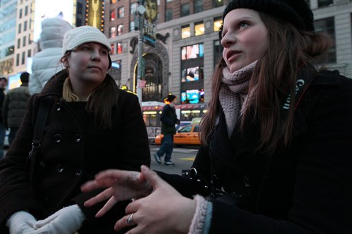 Victoria Melnikow, left, looks on as her sister Cassandra Melnikow is interviewed about news of the Senate approving the repeal of &quotDon't Ask Don't Tell&quot  Saturday Dec. 18, 2010 in New York's Times Square. (AP Photo/Tina Fineberg)