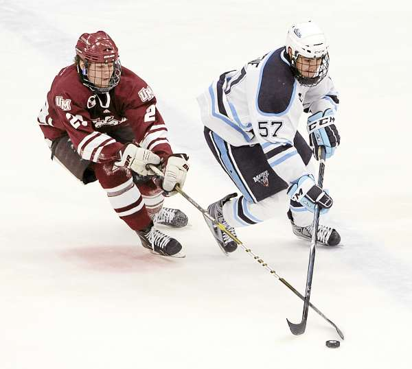 Maine's Matt Mangene (right) and Massachusetts' Marc Concannon battle for the puck during a game on Dec. 12 in Orono. The sophomore played on defense in Maine's Sunday game against the U.S. Under 18 team after spending 17 games as a forward. (BDN File Photo)