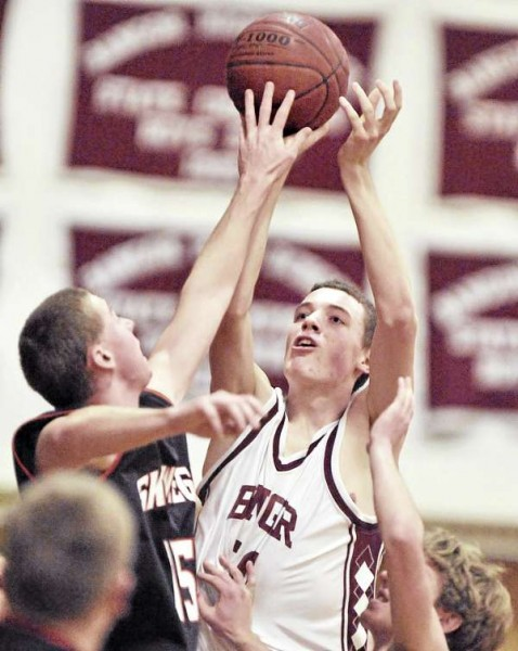 Bangor forward Patrick Stewart (50) pulls up for a short jumper under pressure from Skowhegan defenders Joey Lizzotte (left) and Lucas McDaniels (right) in the first half of their game in Bangor Friday.