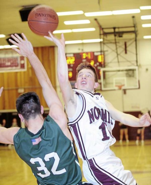 Nokomis' Ruel Libby lays up a shot over Leavitt's Jordan Hersom (left) during the first half of the game in Newport Tuesday evening.
