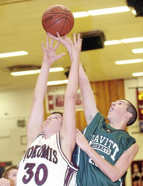Nokomis' Devin Chambers (left) Leavitt's Tim Dow go up for a rebound during the first half of the game in Newport Tuesday evening.