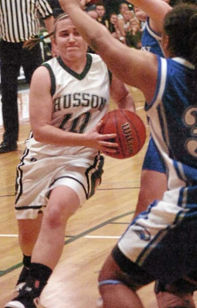 Husson's Caitlyn Butterfield drives past Colby's Jayde Bennett during the first half of the game on Tuesday, January 11, 2011, at Husson University in Bangor.
