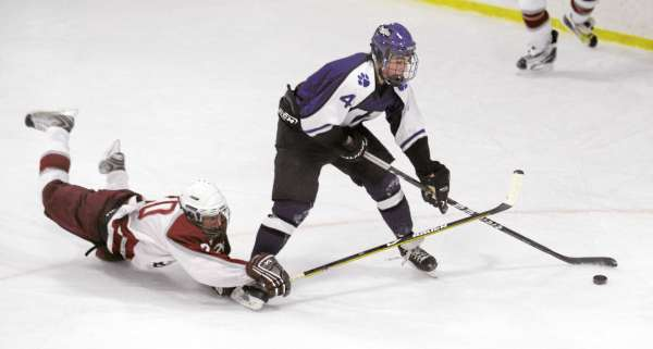 Bangor High School's Wyatt Frost (left) falls onto the ice as he battles for the puck with Waterville High School's Matt Lee during the first period of the game in Bangor Thursday evening.