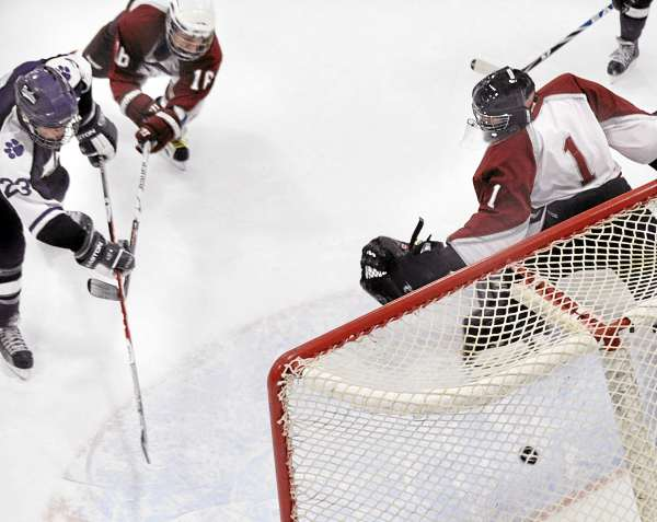 Waterville High School's Tim Locke (left) shoots the puck into the net past Bangor High School's goalie Chris Howat (right) as Bangor's Adam Toth-Javor defends during the first period of the game in Bangor Thursday evening.