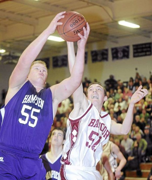 Hampden Academy's Fred Knight (left) and Bangor High School's Patrick Stewart battle for a rebound during the first half of the game in Bangor Friday evening.