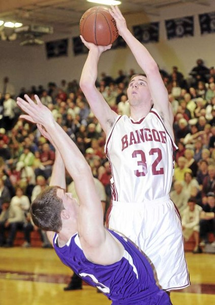 Bangor High School's Zach Blodgett (right) goes up for a shot over Hampden Academy's Graham Safford during the first half of the game in Bangor Friday evening.