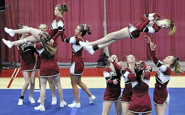 The Bangor High School squad vaults Bailey Dunham (left) and Emma Hardy into the air at the start of their routine in the Class A competition of the KVAC Cheering Championships Monday at the Augusta Civic. Lewiston won the title and Bangor finished fifth.