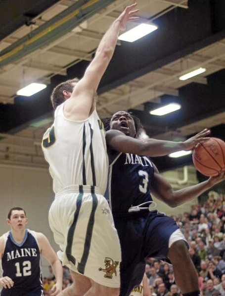Maine's Raheem Singleton (right) is fouled by Vermont's Garrett Kissel on a drive to the basket during first-half America East action Tuesday night at Patrick Gym in Burlington, Vt. Maine beat Vermont 72-58.