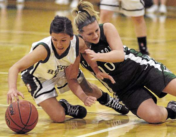 Husson's Amanda Gifford (left) and Castleton's Christine Jaques scramble for a loose ball in the first half of Friday night's game at Newman Gym in Bangor.