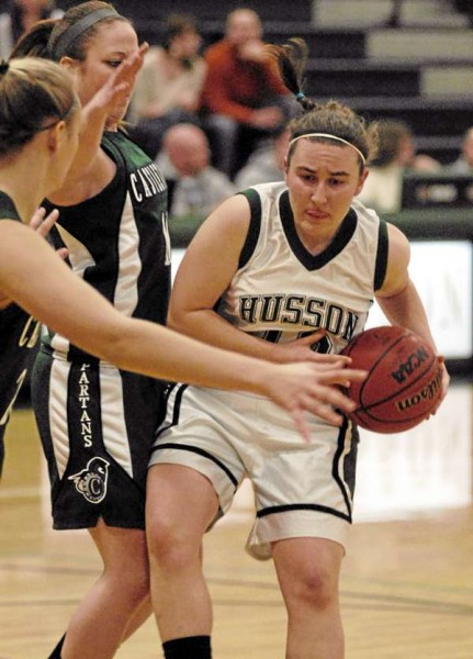 Husson's Caitlyn Butterfield gets by Castleton defender Kelly Conway in first-half action Friday night at Newman Gym.