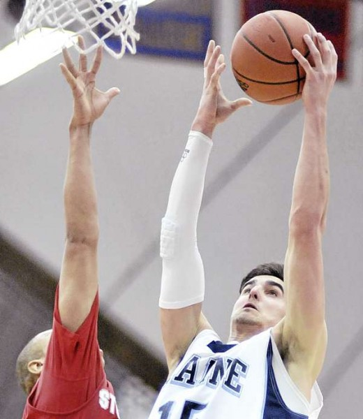 Maine's Troy Barnies (15) gets two points past the defense of Stony Brook's Al Rapier in the second half of their game in Orono Saturday, Jan. 22, 2011.
