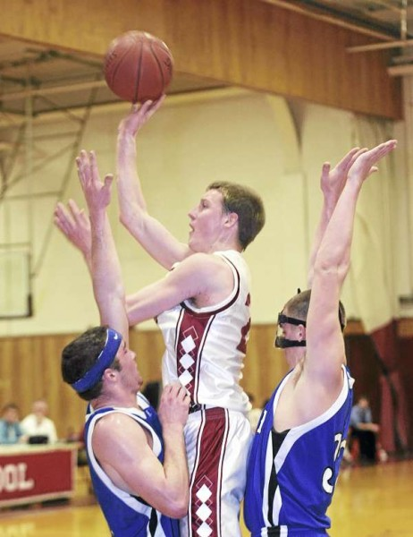 Bangor High School'sTristan Thomas (center) goes up for a shot between Lewiston High School's Steven Patrie (right) and Corbin Hyde  during the first half of the game in Bangor Tuesday evening.