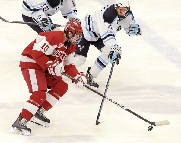 Boston University's Corey Trivino (left) and the University of Maine's Mike Banwell battle for the puck during the first period of the game at Alfond Arena in Orono Friday evening.