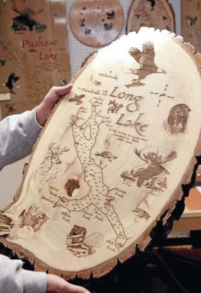 Paul Gagnon shows one of his decorative wood signs of Long Lake.