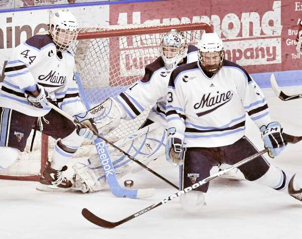 Maine defensemen Ryan Hegarty (44) and Mark Nemec (3) help goalie Martin Ouellette clear a puck in the first period of their game against BU at Orono, Maine Saturday, Jan. 29, 2011.