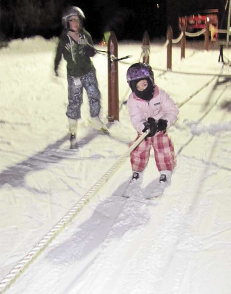 Amya Braley, 4, holds tight on Friday as a rope tow pulls her up the hill at Pinnacle Park in Pittsfield.