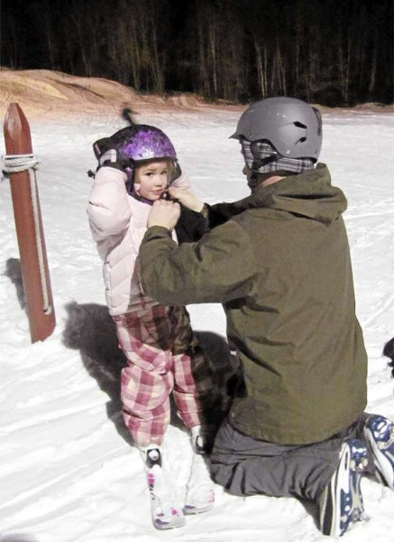 Amya Braley, 4, of Pittsfield, has her helmet adjusted by her father, Cory Braley, on Friday, January 28, 2011 at the Pinnacle in Pittsfield. Amya has been on skis since she was two years old, according to her father.