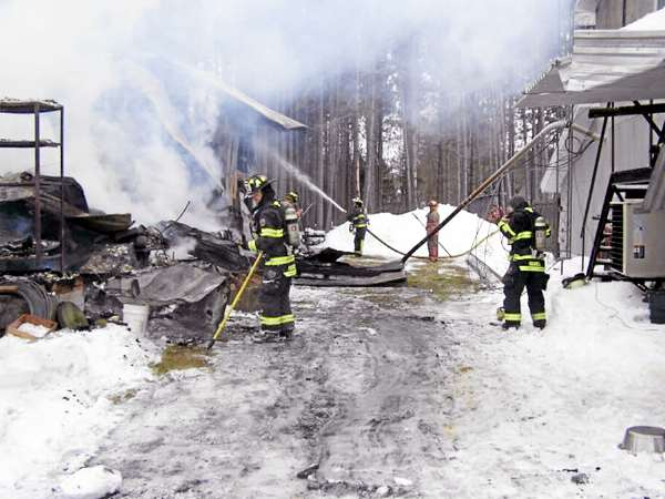 Firefighters from a number of towns responded to a garage fire in Milford just after noon Saturday, Jan. 29, that destroyed structure but saved a nearby home owned by Peter Soucie. The garage was Soucie's machine shop, Milford Fire Chief Chris Matson said. Photos courtesy of Holden and Eddington Fire Chief Jim Ellis Firefighters from a number of towns responded to a garage fire in Milford just after noon Saturday, Jan. 29, that destroyed structure but saved a nearby home owned by Peter Soucie. The garage was Soucie's machine shop, Milford Fire Chief Chris Matson said.  Eddington firefighters Lt. Craig Russell, left, and Capt. David Hughes are pictured in the foreground as other firefighters apply water in the background. Photo courtesy of Holden and Eddington Fire Chief Jim Ellis