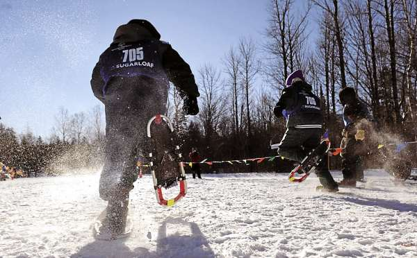 Daigen Pierpont, 11 (left) of the Thomaston Clippers, kicks up the snow as he and other competitors (ages 8-15) make their way down the course in the 100-meter snowshoe dash time trials during the 2011 Special Olympics Maine Winter Games at the Carrabasset Valley Academy Monday, Jan. 31, 2011.