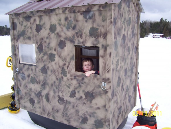 This light weight portable shack is built on a magnum jet sled and measures approximately 4x6 feet. The camo paint job enables this shack to move from the ice to the coyote bait as a heated blind.